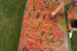 preschoolers making a leaf printed silk play cloth.